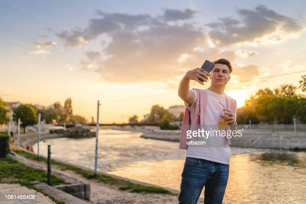 young man making selfies and listening to music by the river - mp3 juices stock photos and pictures
