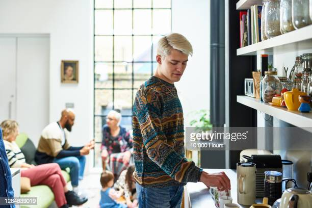 young man making tea in kitchen - preparation stock pictures, royalty-free photos & images