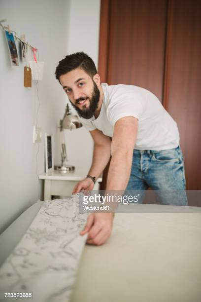 young man making the bed at home - tidy room stock pictures, royalty-free photos & images