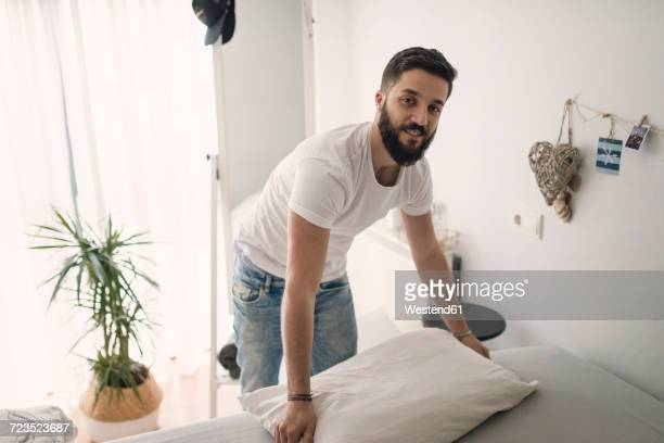 Young man making the bed at home