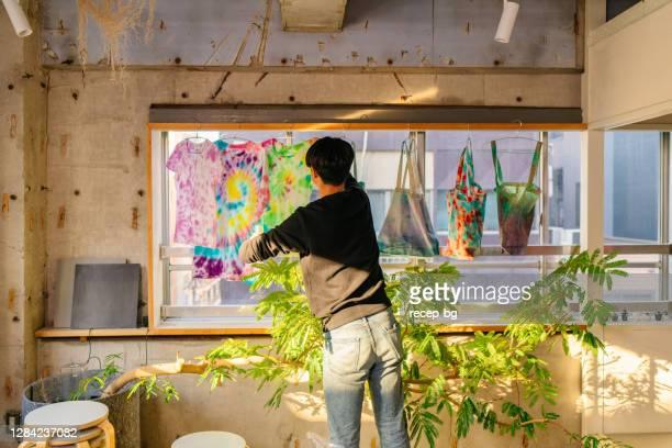屋内でネクタイ染料を作る若い男 - デザイナー服 ストックフォトと画像