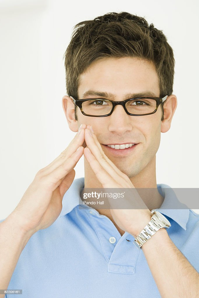 Young man making triangle shape with hands : Stock Photo