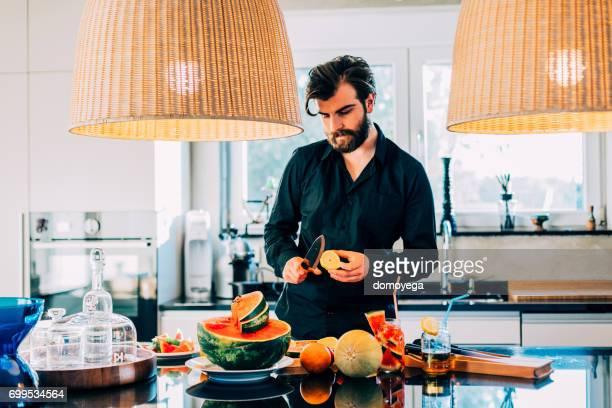 Junger Mann Wassermelonen Salat und Saft in der Küche