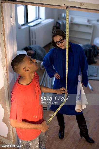 young man measuring door with tape, woman holding blue print - the black tape project stock-fotos und bilder