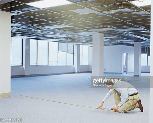 Young man measuring floor in empty office, side view