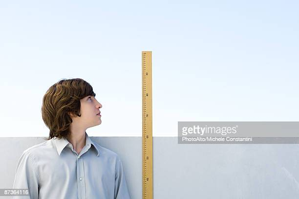 Young man measuring his height with ruler