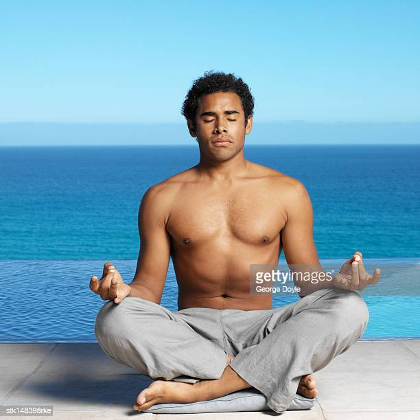 young man meditating beside swimming pool portrait close up