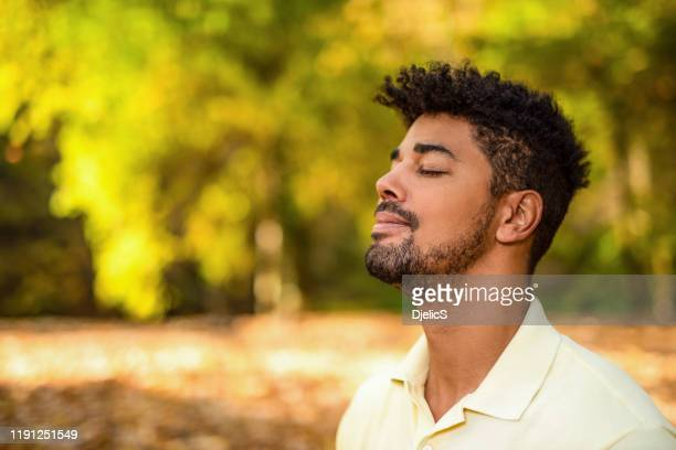 young man meditating in nature on autumn day. - zen like stock pictures, royalty-free photos & images