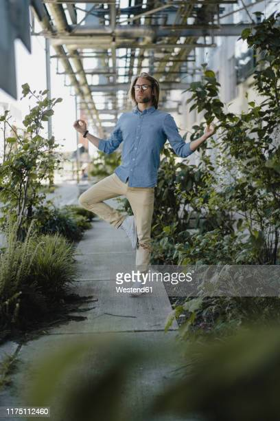 young man meditating on pavement surrounded by plants - solo un uomo foto e immagini stock