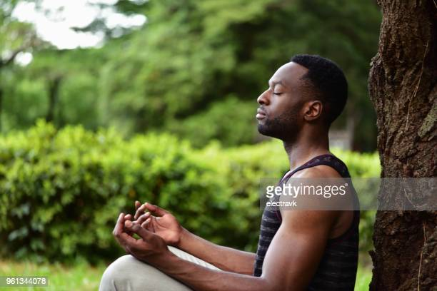 young man meditating - mindfulness stock pictures, royalty-free photos & images