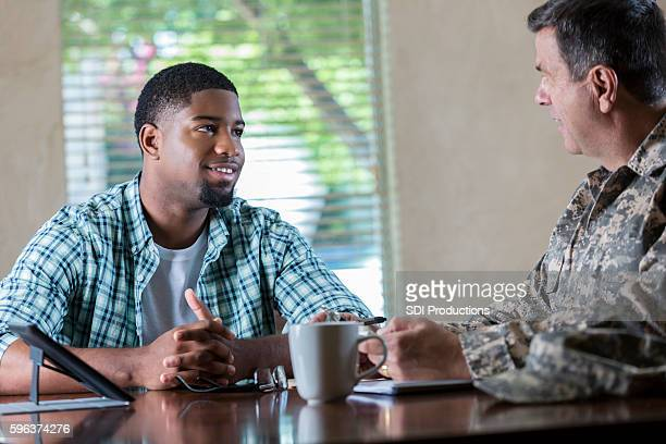 young man meeting with military officer to discuss recruitment - american influenced stock photos and pictures