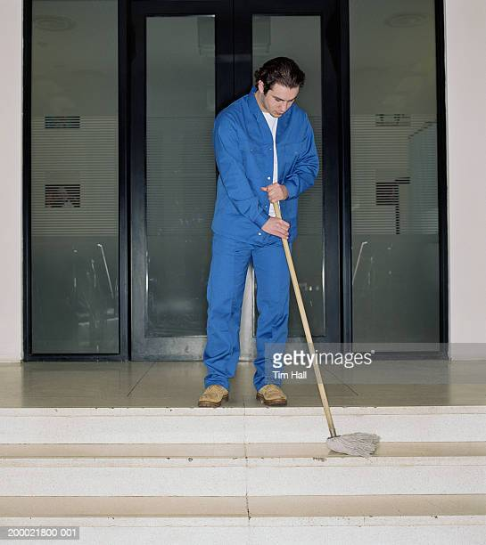 Young man mopping step indoors