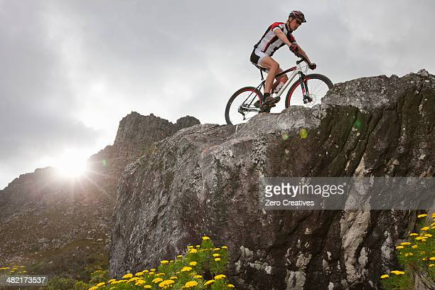 Young man mountain biking on top of rock formation