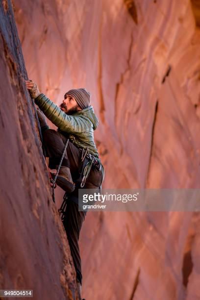 young man mountain climber in moab - rocha vermelha imagens e fotografias de stock
