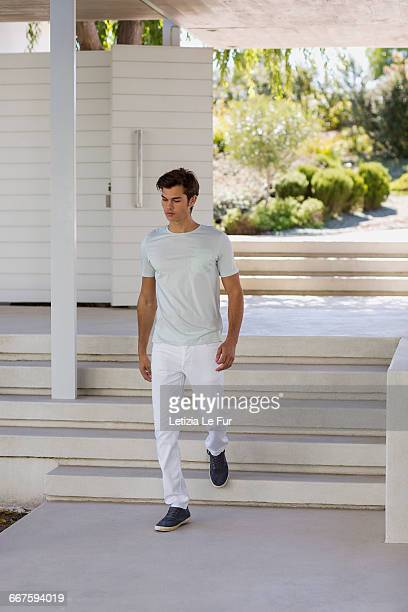 Young man moving down staircases