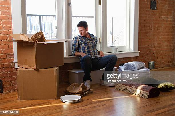 young man moving into new loft apartment - hommes nus photos et images de collection