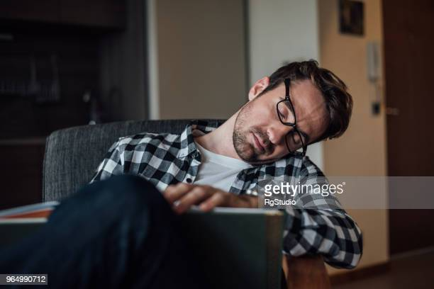 young man napping sitting in chair at home - sonnecchiare foto e immagini stock