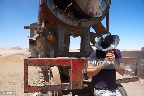 Young man near old train, Bolivia