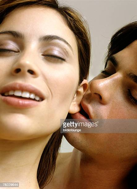 young man nibbling on his girlfriend?s earlobe