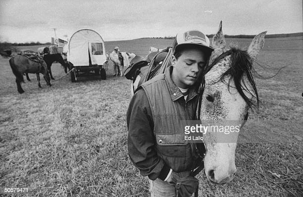 Young man nuzzling up to his horse in open field during a rest stop while reenacting 1000mile Trail of Tears journey that Cherokees traveled 150...