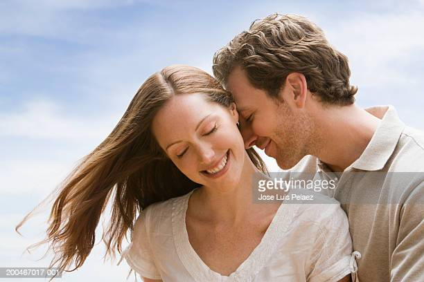 Young man nuzzling woman's ear (Digital Composite)