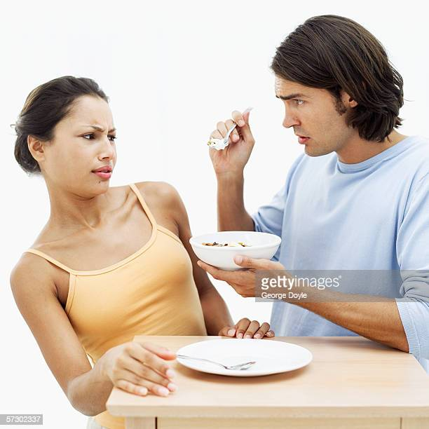 Young man offering bite from bowl to woman