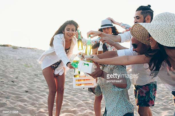 Young man offering drinks on the beach