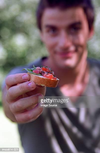 young man offering food. - voorgerecht stockfoto's en -beelden