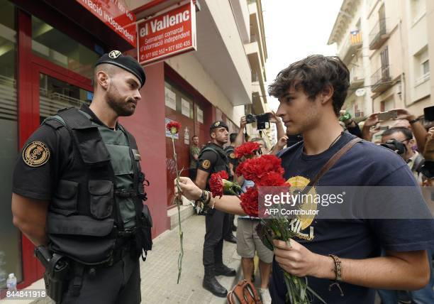 A young man offers a carnation to a civil guard during a protest against a police search in the headquarters of the weekly newspaper El Vallenc in...