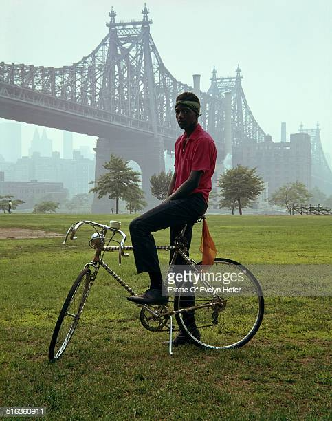 A young man on a bicycle in front of Queensboro Bridge New York 1964