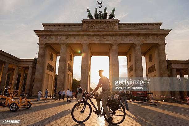 Young man on a bicycle is watching the sunset on the Brandenburg Gate.
