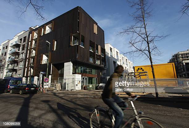 A young man on a bicycle rides past new luxury apartment buildings under construction in Schwedter Strasse in Prenzlauer Berg district on January 17...