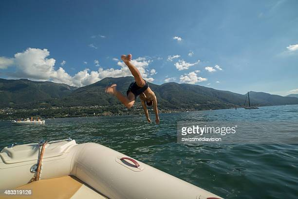 Young man on a boat diving into the water
