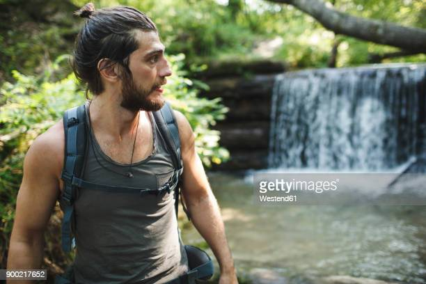 young man on a hiking trip at a waterfall - vie simple photos et images de collection