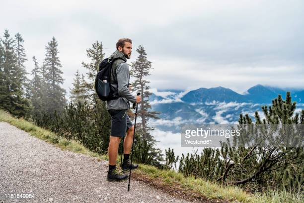 young man on a hiking trip in the mountains looking at view, herzogstand, bavaria, germany - bavarian alps stock pictures, royalty-free photos & images