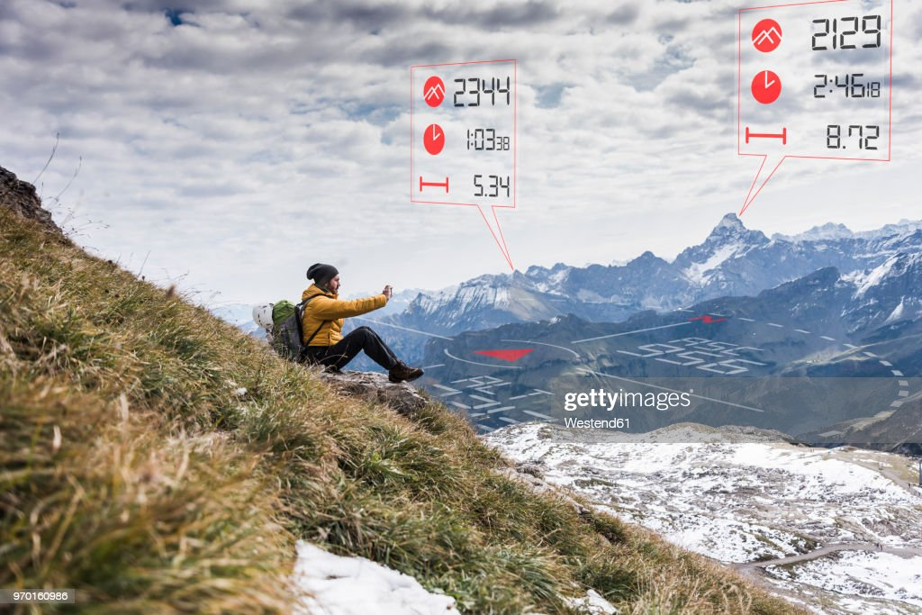Young man on a hiking trip with data emerging from smartphone : Stock Photo