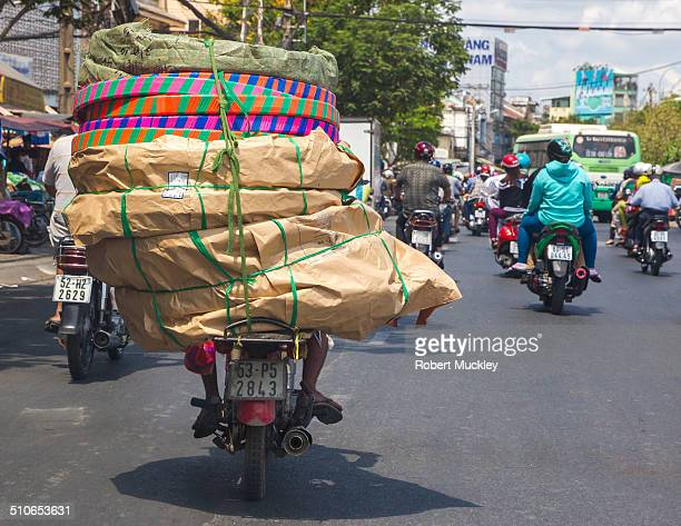 A young man on a moped drives along a Cholon Ho Chi Minh City boulevard with huge load stacked on the passenger seat