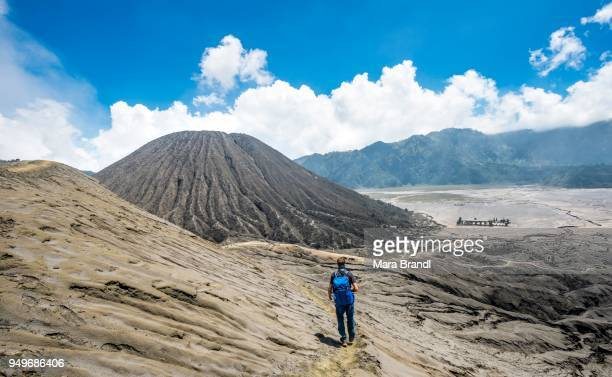 young man on a narrow path at the crater rim of the volcano gunung bromo, behind mt. batok, national park bromo-tengger-semeru, java, indonesia - bromo crater stock pictures, royalty-free photos & images