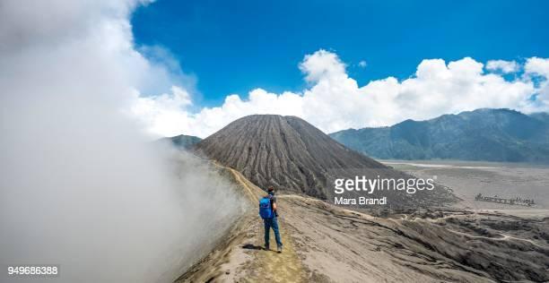 young man on a narrow path at the crater rim, smoking volcano volcano gunung bromo, national park bromo-tengger-semeru, java, indonesia - bromo crater stock pictures, royalty-free photos & images