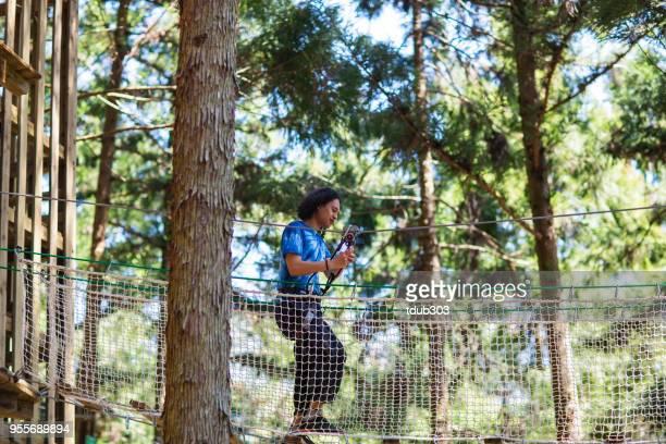 Jovem em uma ponte de corda em uma floresta de obstáculos