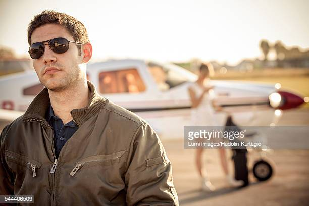 Young man on airfield, woman by airplane in background