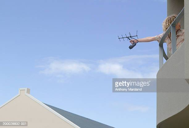 Young man on balcony holding out television aerial