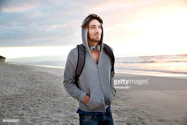 Young man on beach at sunrise