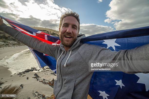 Young man on beach holding Australian's flag