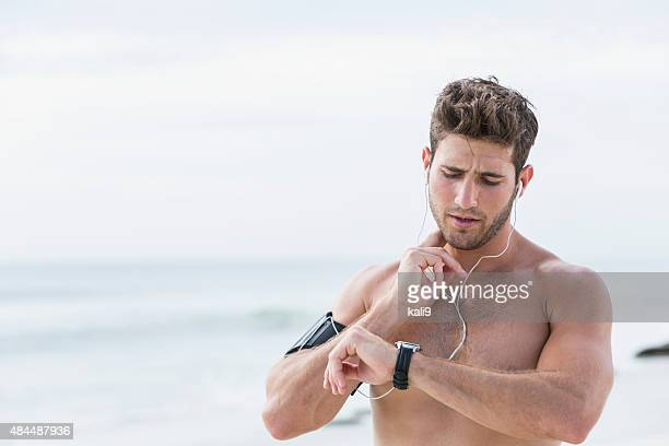Young man on beach taking his pulse