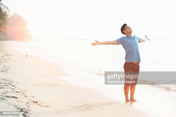 Young man on beach with arms outstretched