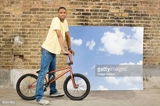 Young man on bicycle by sky backdrop
