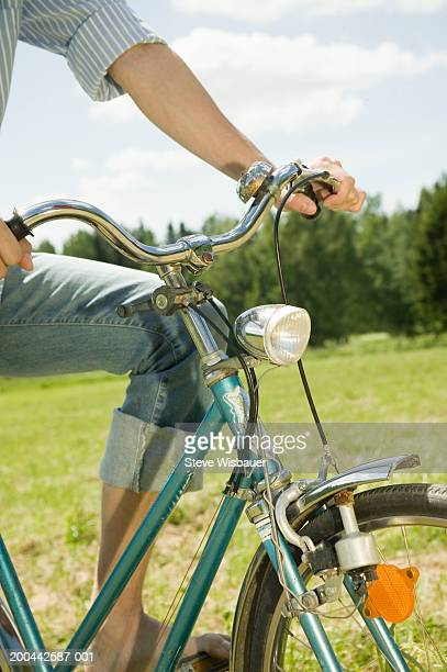 Young man on bicycle, close-up of handlebars
