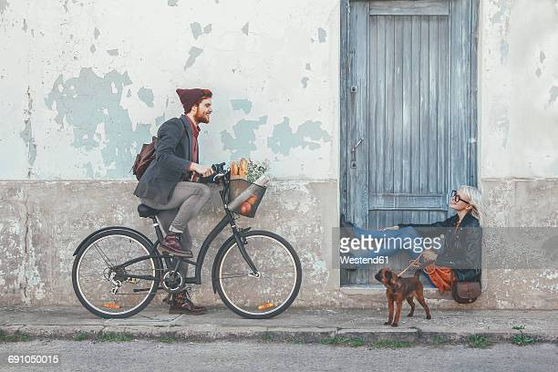 Young man on bicycle smiling at woman with dog