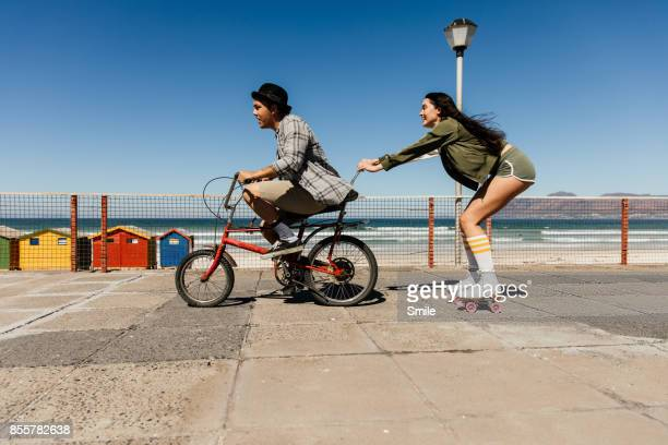 young man on bicycle towing girl on roller skates - roller skating stock photos and pictures